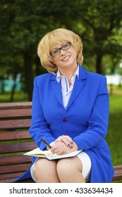 Close up portrait of a beautiful middle aged woman in a blue business suit, summer outdoors