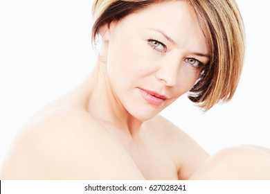 Close up portrait of beautiful middle aged woman with short hair hugging her knees over white background - beauty, skin care or anti aging concept