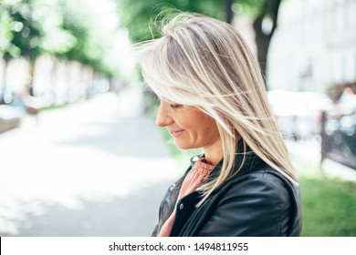 Close up portrait of a beautiful modest young blonde woman in profile. The girl smiles and looks down embarrassed. Alley with trees is in the background