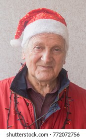 Close up portrait of a beautiful old joyful business man dressed in a Santa Claus hat smiling and looking happily at the camera.