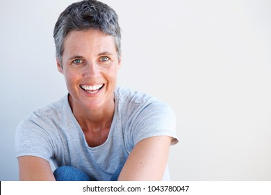 Close up portrait of beautiful older woman smiling against white wall