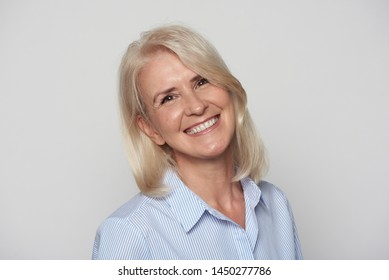 Close up portrait of beautiful older woman smiling isolated on grey background