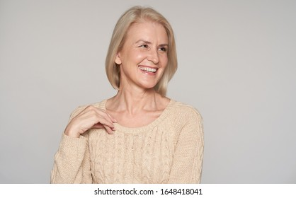 Close up portrait of beautiful older woman smiling. Isolated on grey