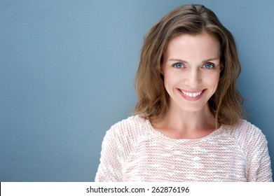 Close up portrait of a beautiful older woman smiling with sweater on blue background