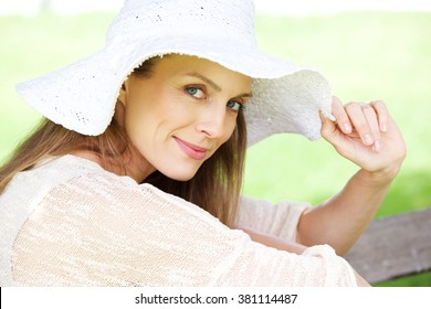 Close up portrait of a beautiful older woman smiling with hat