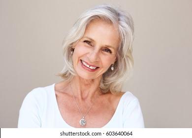 Portrait en gros plan d'une belle femme âgée souriante et debout au mur