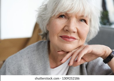 Close up portrait of beautiful positive middle aged Caucasian lady on retirement daydreaming at home, thinking about her grandchildren. Elegant gray haired grandmother spending time indoors