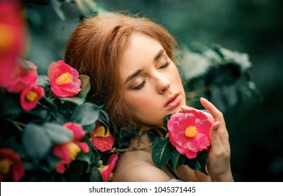Close up portrait of a  beautiful red hair girl in a pink vintage dress  standing near colorful flowers. Art work of romantic woman .Pretty tenderness model dreaming.