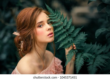 Close up portrait of a  beautiful red hair girl in a pink vintage dress standing on green background. Art work of romantic woman .Pretty tenderness model looking at camera.