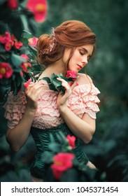 Nahaufnahme eines schönen roten Haarmädchens in einem rosa Vintage-Kleid, das in der Nähe von bunten Blumen steht. Kunstwerk der romantischen Frau. Hübsches Traummodell.