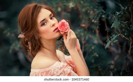 Close up portrait of a  beautiful red hair girl in a pink vintage dress  standing near colorful flowers. Art work of romantic woman .Pretty tenderness model looking at camera.
