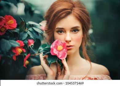 Nahaufnahme eines schönen roten Haarmädchens in einem rosa Vintage-Kleid, das in der Nähe von bunten Blumen steht. Kunstarbeit von Romantikerin. Hübsches Zärtheitsmodell mit Kamera.