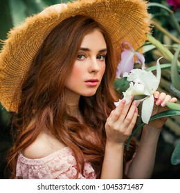 Close up portrait of a  beautiful red hair girl in a pink vintage dress and straw hat standing near colorful flowers. Art work of romantic woman .Pretty tenderness model looking at camera.