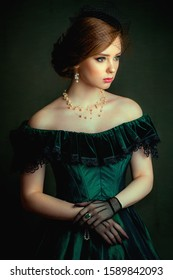 Close up portrait of a  beautiful red hair girl in a green vintage dress, jewelry and black veil on her face. Art work of romantic woman .Pretty tenderness model looking at camera.