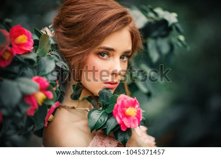 Close up portrait of a beautiful red hair girl in a pink vintage dress  standing near 448312f298a2
