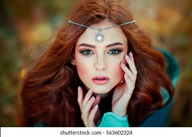 Close up portrait  of Beautiful red haired girl in green medieval dress and black accessories on head looking at camera. Fairy tale story about brave heart woman.Warm art work