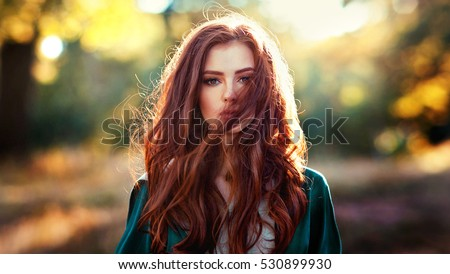 Close up portrait of  a beautiful red haired girl in green medieval dress on glowing sun. Fairy tale story about brave heart woman.Amazing model looking at camera.Warm art work