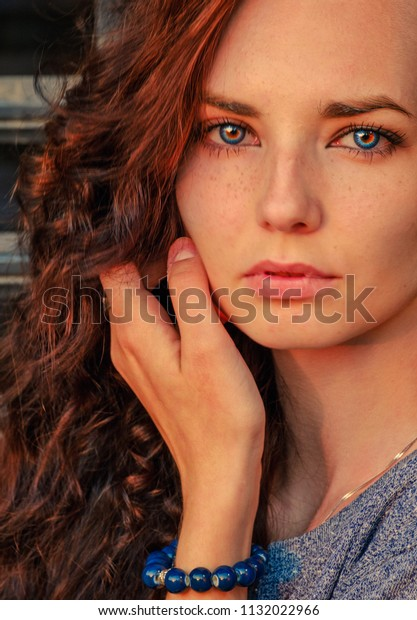 Close up portrait of a beautiful red haired girl touching her face by hand. Amazing model looking at camera. Warm art work toned