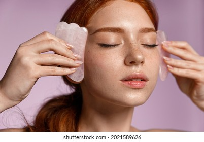 Close up portrait of beautiful redhead girl, ginger female massaging face with jade scraper, close eyes, doing tcm cosmetology procedure, purple background