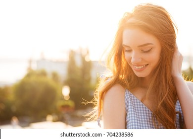 Close up portrait of a beautiful redhead girl playing with hair while standing and posing outdoors with a city view