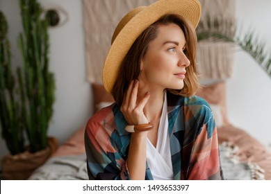 Close up portrait of beautiful romantic woman in straw hat chilling over bohemian interior.woo accessories.