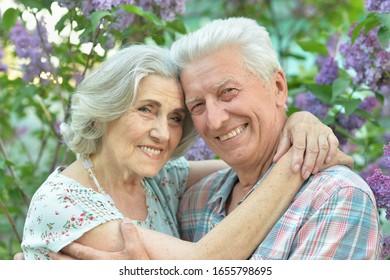 Nahaufnahme eines schönen älteren Ehepaares, das auf lila Hintergrund im Park umarmt ist