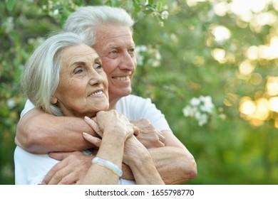 Nahaufnahme eines schönen älteren Ehepaares, das im Frühlingspark umarmt und posiert