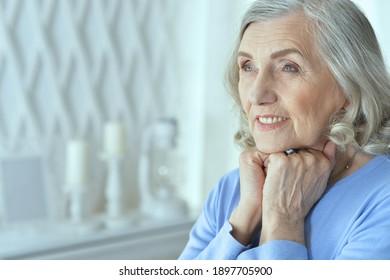 Close up portrait of beautiful senior woman posing at home