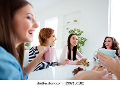 Close up portrait beautiful she her ladies buddies meeting sit round big white table bright kitchen hold cups listen rumours gossip secrets news having fun girls day night holiday