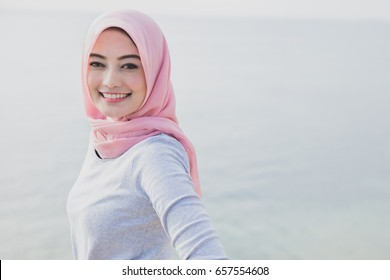 close up portrait of beautiful smile of asian woman wearing hijab at the beach