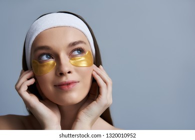 Close up portrait of beautiful smiling lady with masks under lower eyelids gently touching her face and looking up dreamily. Isolated on blue background