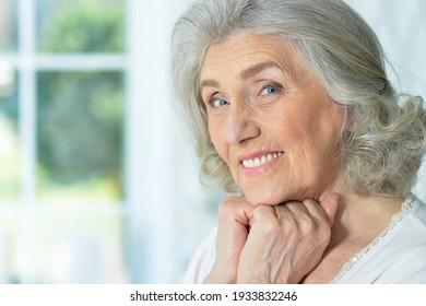 Close up portrait of beautiful smiling senior woman posing at home
