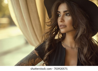 Close up portrait of beautiful tanned glam tattooed model with long wavy hair wearing black dress and wide brimmed hat looking aside, sandy yellow curtains on the background