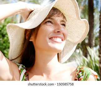 Close up portrait of a beautiful tourist woman wearing a woven straw wide beam hat with the sunshine filtering through the pattern and casting a textures shadow on her face, smiling.