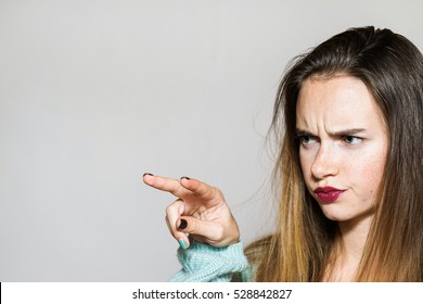 Close up portrait of beautiful Unhappy woman with red lips and bright makeup showing a sign with your fingers, I'm watching you.Angry face expression.Isolated over white background