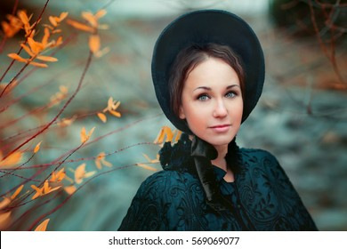Close up portrait of a beautiful  in vintage black dress.Romantic lady enjoying the nature and posing on autumn colorful background.