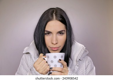 Close up portrait of a beautiful woman holding and drinking a hot and comforting cup of tea or coffee beverage, warming up in the cold winter
