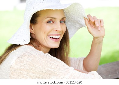 Close up portrait of a beautiful woman laughing with sun hat