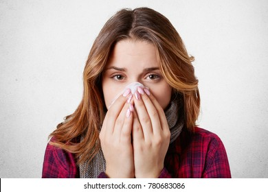 Close up portrait of beautiful woman sneezes and coughs, uses tissue, rubs nose, has bad cold, isolated over white background. Low spirited desperate woman suffers from cold and running nose