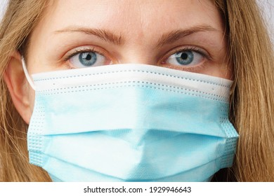 Close up portrait of a beautiful woman wearing a protective mask. A man calmly looking at the camera.