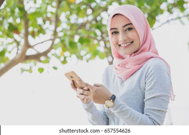 close up portrait of beautiful woman wearing hijab smiling while texting on mobilephone