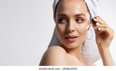 Close up portrait of beautiful woman in white towel with perfect skin applying moisturizing facial serum for healthy soft glowing skin isolated on white background. Morning luxury beauty routine