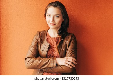 Close up portrait of beautiful young 25-30 year old woman with professional make up, wearing brown leather jacket