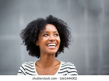 Close up portrait beautiful young african american woman smiling by gray wall and looking up