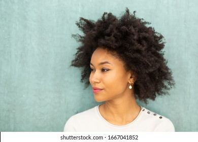 Close up portrait beautiful young african american woman with afro hair by green background