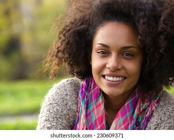 Close up portrait of a beautiful young african american woman smiling outdoors