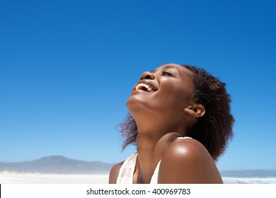 Close up portrait of beautiful young african woman laughing outdoors against sky