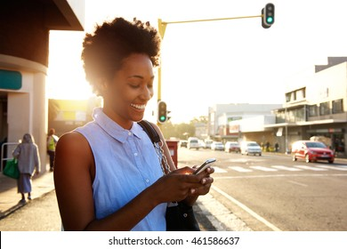 Close up portrait of beautiful young african woman using cellphone outdoors in the city