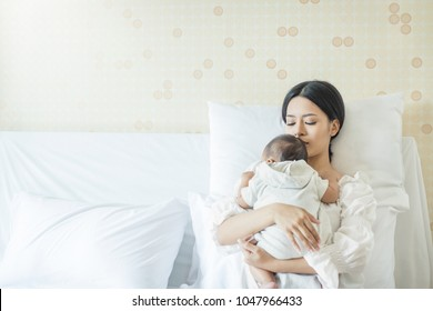 Close up portrait of beautiful young asian mother with newborn baby, copy space with bed in the hospital. Healthcare and medical love lifestyle mother'??s day concept