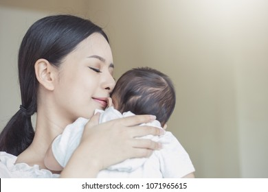 Close up portrait of beautiful young asian mother kissing her newborn baby. Healthcare and medical love lifestyle mother'??s day concept